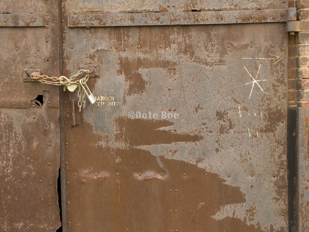 Close up of an old metal door locked with a padlock and chain