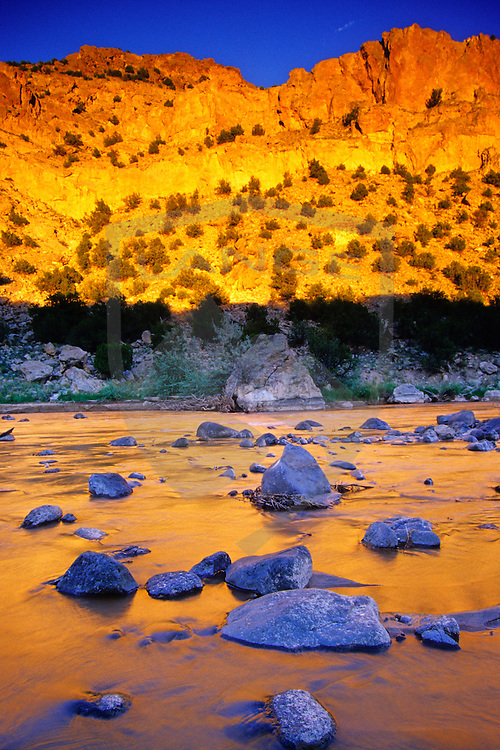 intense sunset light in hues of orange, yellow and red strike high desert badlands mesas and are reflected in the river below.  such beautiful nature scenery can be found along the rio chama river in northern new mexico, usa.