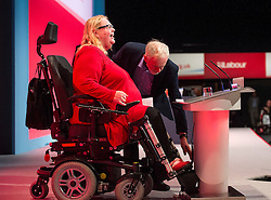 **CAPTION CORRECTION. Spelling of ATHERTON wrong in first send** © Licensed to London News Pictures. 28/09/2015. Brighton, UK. New Shadow Chancellor JOHN MCDONNELL and labour leader JEREMY CORBYN helping free former councillor and Labour party activist CANDY ATHERTON  when her wheelchair got stuck on the podium on  Day two of the 2015 Labour Party Conference, held at the Brighton Centre in Brighton, East Sussex. This years conference takes place just weeks after Jeremy Corbyn was elected leader of the party. Photo credit: Ben Cawthra/LNP