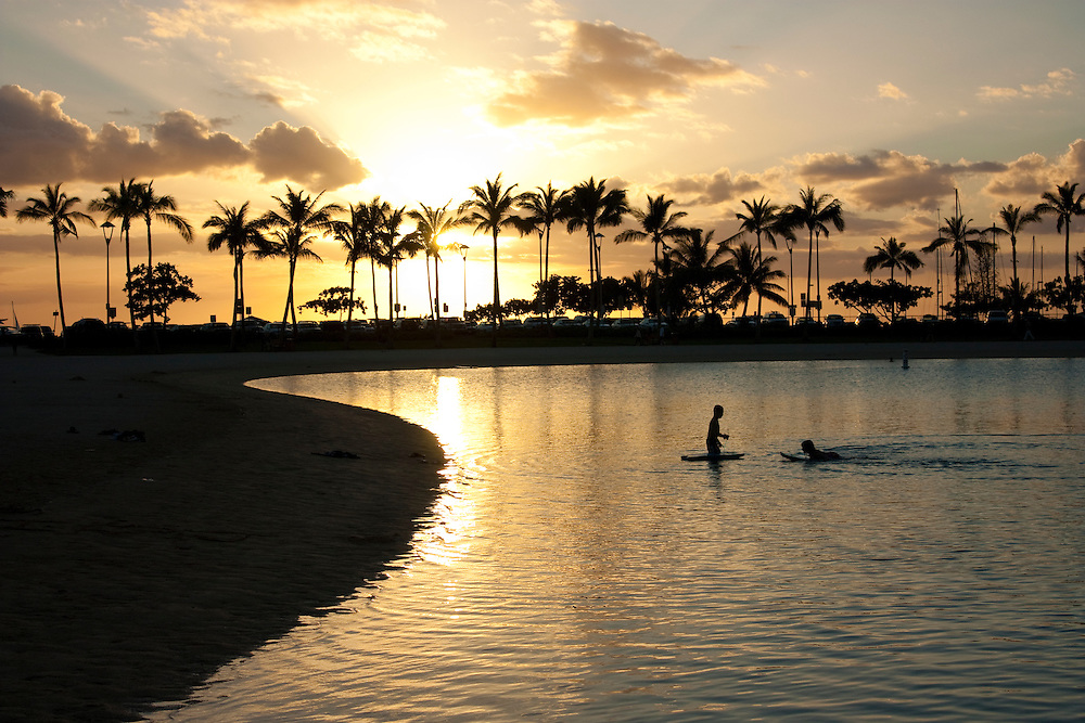 Two boys playing in calm lagoon, Hilton Village, Waikiki, Honolulu, Hawaii