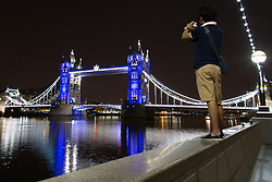 © Licensed to London News Pictures. 23/07/2013. London, UK. A man stands on a wall leaning over the River Thames to photograph blue Tower Bridge. Tower Bridge is illuminated in blue at night on 23 July 2013 to celebrate the Duchess of Cambridge giving birth to a baby boy and the future King of England. Photo credit : Vickie Flores/LNP