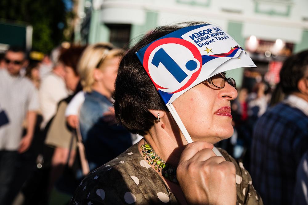 A woman hidding herself from the sun with a small Tadic flag / Une femme se cache du soleil avec un petit drapeau de soutien à Tadic