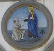 Relief vignette detail from the outside of the Alinari National Museum of Photography (Museo Nazionale Alinari della Fotografia) in Florence, Italy. Painted relief images of Christ, Mary, and related Saints adorn the building in the space above each column.