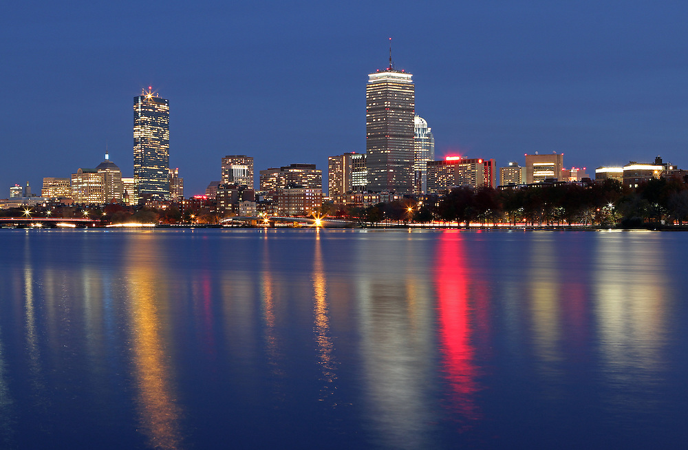 Boston skyline photography image featuring famous architecture landmarks such as the Boston Prudential Center, John Hancock Building and Back Bay brownstones reflected in the Charles River. The cityscape photograph was taken in November at twilight minutes after sunset.<br />