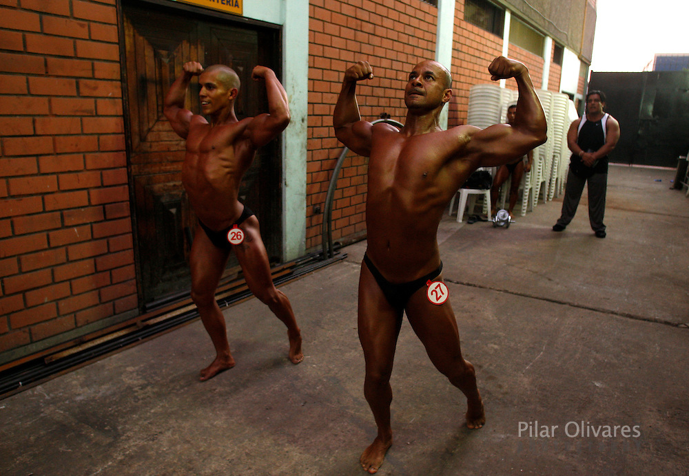 Competitors flex their muscles as they wait to participate in a bodybuilding competition in Lima January 30, 2010.