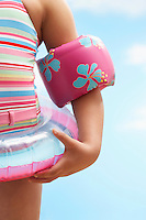 Girl (7-9 years) wearing inflatable ring and water wings mid section
