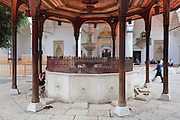 The sadrvan or fountain, used to wash before entering the mosque, with a stone basin under a carved wooden canopy, in the courtyard of the Gazi Husrev-beg Mosque, built 1530-32, Sarajevo, Bosnia and Herzegovina. The complex includes a maktab and madrasa (Islamic primary and secondary schools), a bezistan (vaulted marketplace)and a hammam. The mosque was renovated after damage during the 1992 Siege of Sarajevo during the Yugoslav War. Picture by Manuel Cohen