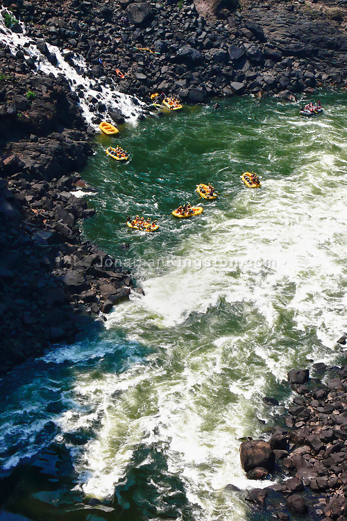 Visitors of Victoria Falls Naitonal Park go white water rafting down the Zambezi River in yellow river rafts.