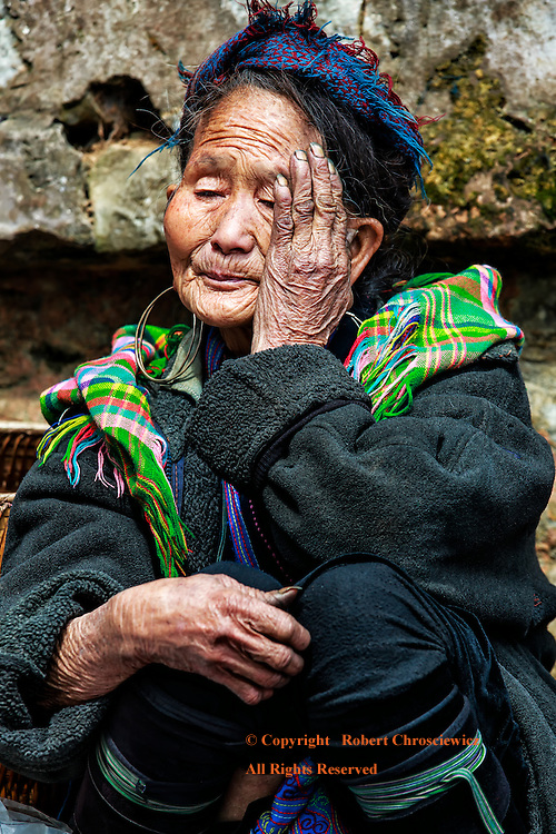 An elderly woman of the a local hill tribe, the Black Hmong, rests for a moment from a futile attempt to sell her craft work, Sapa Vietnam.