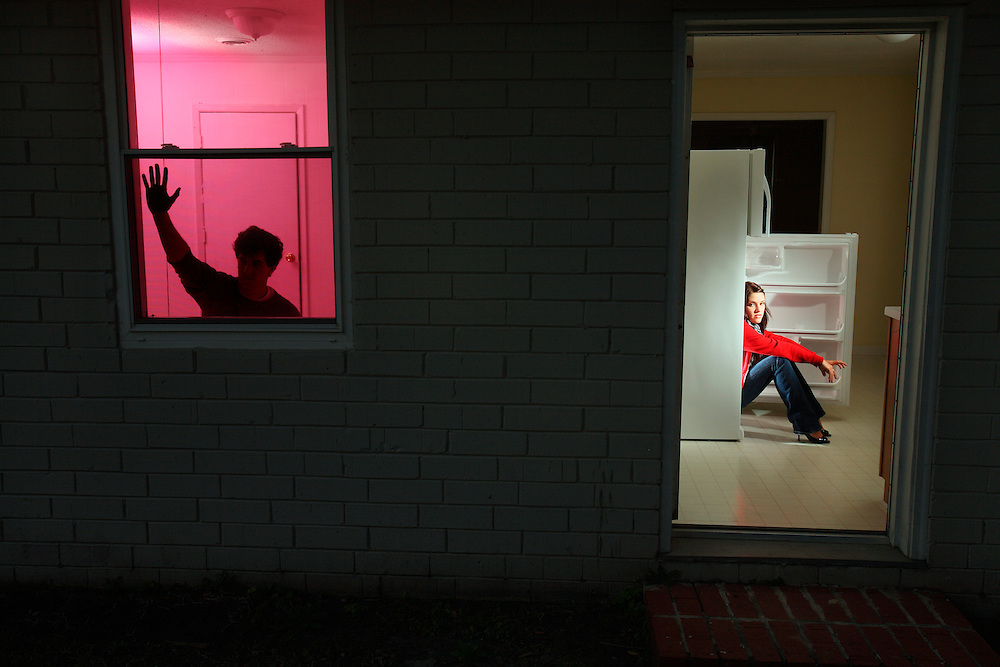 A woman gets out of a refrigerator at night while a man waits in the next room.