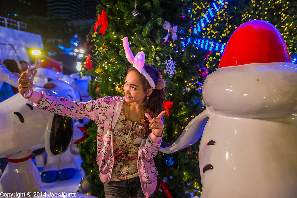 """17 DECEMBER 2014 - BANGKOK, THAILAND: A woman takes a """"selfie"""" in front of a  Christmas tree at Central World in Bangkok. Thailand is overwhelmingly Buddhist. Christmas is not a legal holiday in Thailand, but Christmas has become an important commercial holiday in Thailand, especially in Bangkok and communities with a large expatriate population.    PHOTO BY JACK KURTZ"""