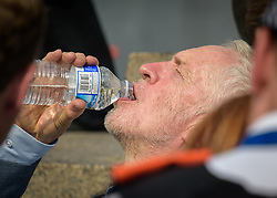 © Licensed to London News Pictures. 13/07/2018. London, UK. Labour Party leader JEREMY CORBYN is seen drinking water in warm weather conditions as Tens of thousands of demonstrators march through central London to protest against the President of the United States, Donald Trump, and his ongoing four-day visit to the UK. The demonstration began at Portland Place and ended with a rally at Trafalgar Square. Photo credit : Andre Camara/LNP