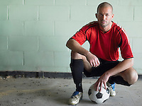 Soccer player crouching with ball portrait
