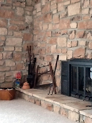 Stone fireplace with a glass door has various old tools, fireplace tools and even a picnic hamper full of stuffed dogs next to it