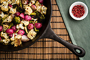 Roasted radish, cauliflower, and broccoli with pink pepprocorns.