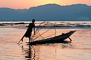 Traditional Intha tribe paddle flat-bottomed skiff boats by leg-rowind - with one leg wrapped around a single wooden paddle to drive the blade through the water in a snake-like motion, Inle Lake, B?urma