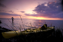 A kayak rests while its owner fishes.