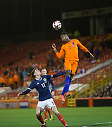 f9th November 2017, Pittodrie Stadium, Aberdeen, Scotland; International Football Friendly, Scotland versus Netherlands; Holland's Quincy Promes leaps high above Scotland's Ryan Christie