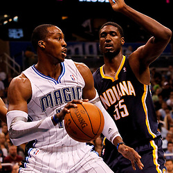 March 11, 2012; Orlando, FL, USA; Orlando Magic center Dwight Howard (12) is defended by Indiana Pacers center Roy Hibbert (55) during the second quarter of a game at  Amway Center.   Mandatory Credit: Derick E. Hingle-US PRESSWIRE