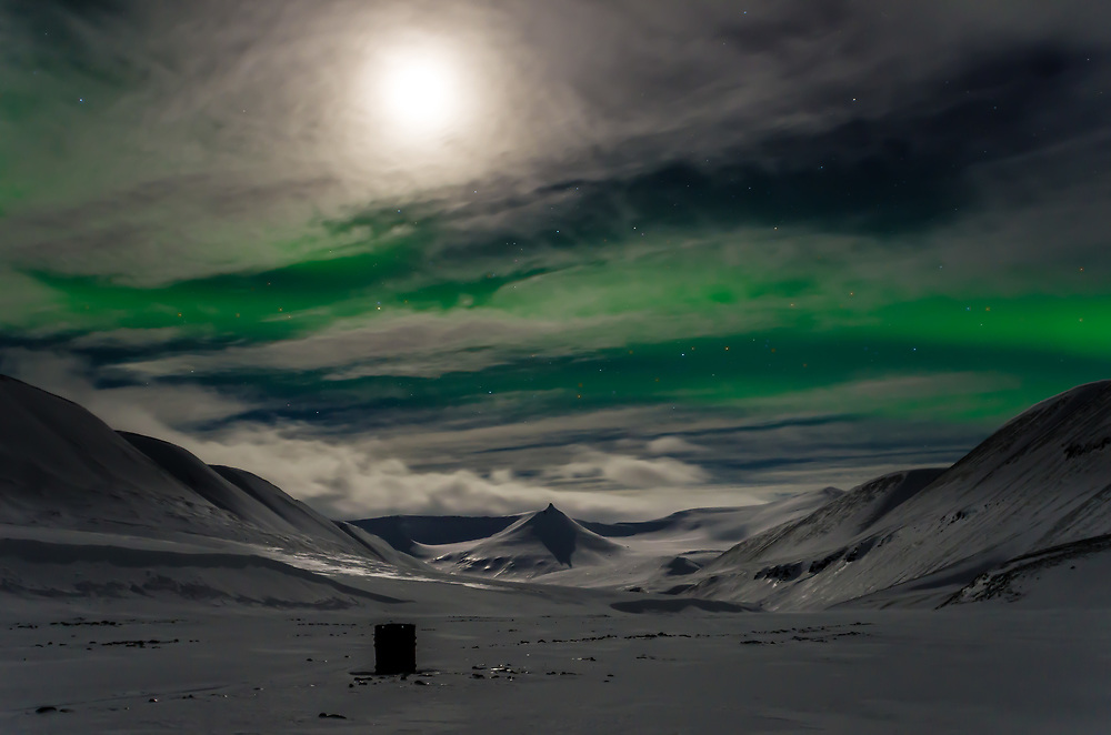 An old barrel stands in the polar night in Bjørndalen on Svalbard. The night is lit by moonshine complimented by a splash of aurora borealis.
