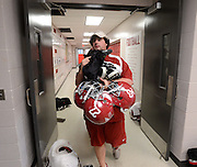 Equipment managers work in the Mal Moore Athletic Facility to get the University of Alabama football team ready for the trip to Baton Rouge to face LSU.  Michael Neese carries a load of helmets after practice to get them packed for the trip.  Photo by Gary Cosby Jr.