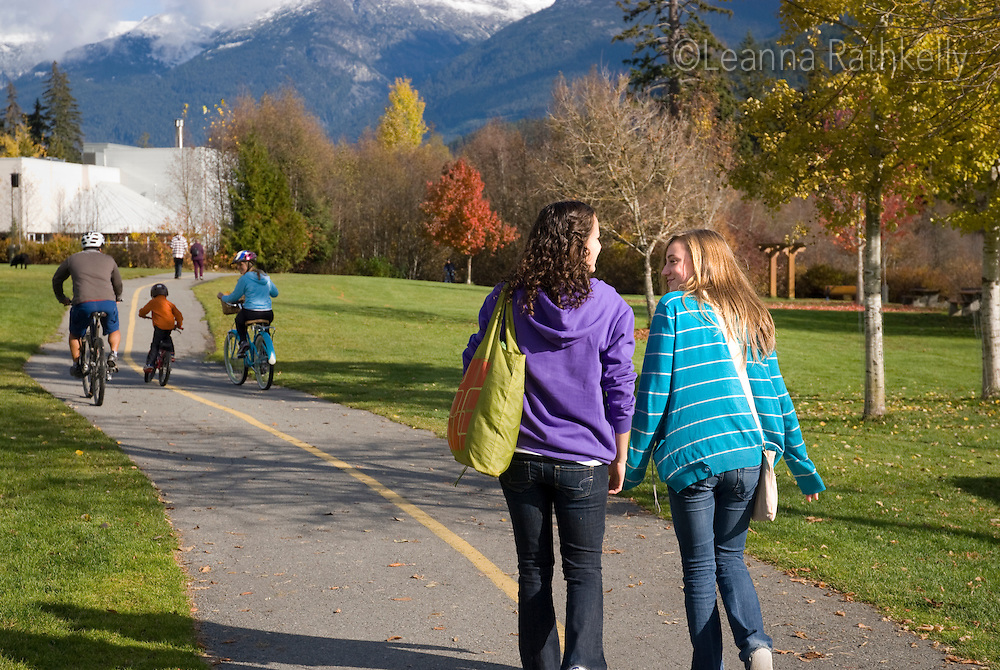 Teenage girls walk  along the trail near Meadow Park Recreation Centre, along the River of Golden Dreams. Whistler Mountain rises in the background.