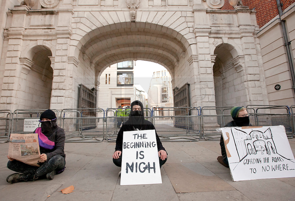 © Licensed to London News Pictures. 17/10/2011. LONDON, UK. Three Occupy London protesters sit outside an entrance to Paternoster Square, home of the London Stock Exchange, as the demonstration enters its third day. As part of a demonstration taking place in cities across the world Protesters occupied the square outside St Paul's Cathedral on Saturday (15/10/11) as part of a protests taking place in cities across the world demonstrating against the banks handling of the current ongoing financial crisis . Photo credit: Matt Cetti-Roberts/LNP