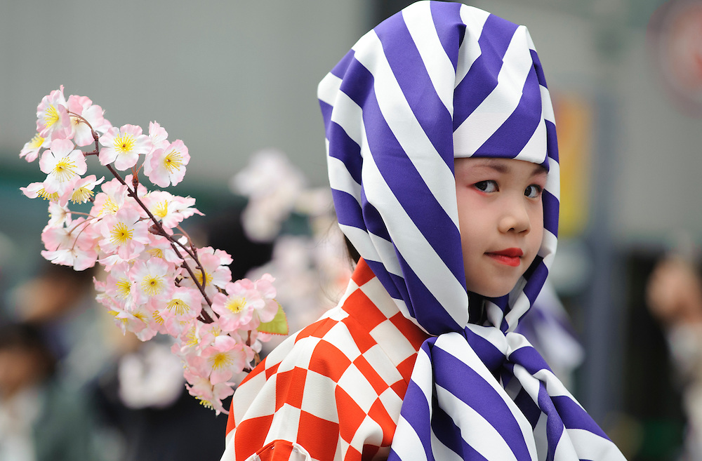 A young girl in traditional Japanese traveling clothing walks in a parade at the Nagoya Festival in Nagoya, Japan.