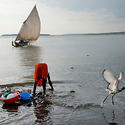 Kenya. Mbita on shore of Lake Victoria. Homa Bay county. Young girl washing dishes in the lake.
