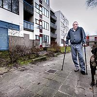 Nederland, Amsterdam , 20 januari 2014.<br /> Bewoners van wooncomplex Louweshoek in Slotervaart zijn geschokt door de zoveelste blunder met betrekking tot asbest.<br /> Gisteren maakte wooncorporatie Woonzorg Nederland bekend dat er tóch asbestdeeltjes in een woning zijn gevonden, terwijl het huis eerder veilig was verklaard. De bewoner van de woning is hierdoor besmet geraakt met de gevaarlijke stof. Buurtbewoners vinden het een schande en hebben geen vertrouwen meer in een goede afloop.<br /> Op de foto bewoner Mike Bron en zijn hond.<br /> <br /> Foto:Jean-Pierre Jans