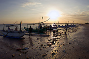 Fishermen launching their jukungs at sunset from the beach in Bali, Indonesia.
