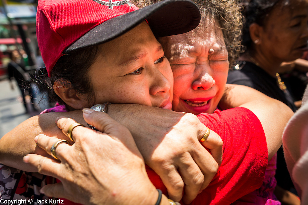 "25 MAY 2014 - BANGKOK, THAILAND: Thai ""Red Shirt"" supporters of the ousted civilian government cry at a demonstration against the military junta. A family member of the woman on the left had been arrested by soldiers. Public opposition to the military coup in Thailand grew Sunday with thousands of protestors gathering at locations throughout Bangkok to call for a return of civilian rule and end to the military junta.     PHOTO BY JACK KURTZ"