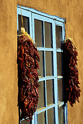 "North America, United States, New Mexico, Santa Fe, ""ristra"" strands of dried chili peppers hanginng by window of adobe house"