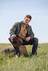 cowboy sitting on a rock in a field