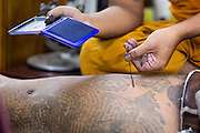 """22 MARCH 2013 - NAKHON CHAI SI, NAKHON PATHOM, THAILAND: Detail photo of a monk giving a man a Sak Yant sacred tattoo at Wat Bang Phra. Wat Bang Phra is the best known """"Sak Yant"""" tattoo temple in Thailand. It's located in Nakhon Pathom province, about 40 miles from Bangkok. The tattoos are given with hollow stainless steel needles and are thought to possess magical powers of protection. The tattoos, which are given by Buddhist monks, are popular with soldiers, policeman and gangsters, people who generally live in harm's way. The tattoo must be activated to remain powerful and the annual Wai Khru Ceremony (tattoo festival) at the temple draws thousands of devotees who come to the temple to activate or renew the tattoos. People go into trance like states and then assume the personality of their tattoo, so people with tiger tattoos assume the personality of a tiger, people with monkey tattoos take on the personality of a monkey and so on. In recent years the tattoo festival has become popular with tourists who make the trip to Nakorn Pathom province to see a side of """"exotic"""" Thailand. The 2013 tattoo festival was on March 23.    PHOTO BY JACK KURTZ"""