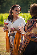 Woman enjoys a summer afternoon at Archery Summit's 'Swine & Wine' event at their Dundee Hills vineyard,  Willamette Valley, Oregon