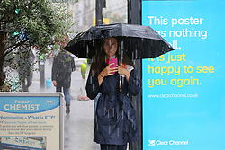 © Licensed to London News Pictures. 18/06/2020. London, UK. A woman shelter from heavy rain underneath an umbrella in north London.  Photo credit: Dinendra Haria/LNP