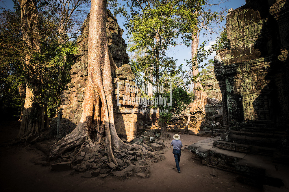 A man walking past trees engulfing the buildings at Ta Prohm Temple, Cambodia