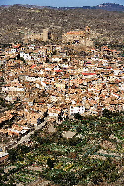 View of tile roofed village of Cornago, with gardens in the foreground, La Rioja, Spain.