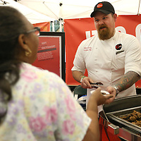 Adam Robison | BUY AT PHOTOS.DJOURNAL.COM<br /> Ryan McCoy, Executive Chef at the Grill in Tupelo, hands Wanda Sims, of Tupelo, petite tenderloin marinaded in soy, ginger, pinapple and garlic, during the Taste of Tupelo at the BancorpSouth Arena Thursday night.