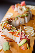 A dragon roll with wasabi and lemon slices.