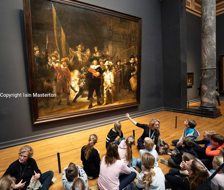Schoolchildren visitors at The Night Watch painting by Rembrandt van Rijn at the Rijksmuseum in Amsterdam, The Netherlands