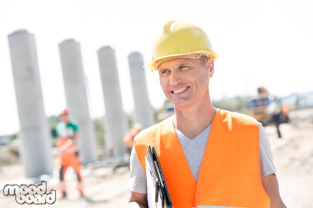 Happy architect looking away while holding clipboard at construction site