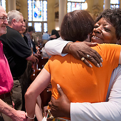 2 AUG. 2015 -- ST. LOUIS --   Sandi E. Garland (right) and Tina Clarkin embrace worshipers share the Sign of Peace during Mass Mob III at Sts. Teresa and Bridget Catholic Parish in St. Louis Sunday, Aug. 2, 2015. Kevin Clarkin, Tina Clarkin's husband, is at left. The event brings Catholics from across the Archdiocese of St. Louis to worship at historic, urban parishes.<br /> <br /> Photo by Sid Hastings.