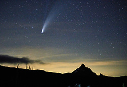 Comet Neowise appears in the night sky over Oregon's Mount Washington on July 17, 2020. Both the comet's tails are visible. According to NASA, the lower tail, which appears broad and fuzzy, is the dust tail created when dust lifts off the surface of the comet's nucleus and trails behind the comet in its orbit. The less visible upper tail is the ion tail, which is made up of gases that have been ionized by losing electrons in the sun's intense light.<br /> <br /> The comet is named after the telescope that first discovered it in March, 2020, the Near Earth Orbit Wide-field Infrared Survey Explorer. Launched in 2009, the telescope's mission was to find any object that could pose an impact hazard to the Earth. According to NASA, the comet, about 3 miles in diameter, will pass harmlessly by the Earth at a distance of about 63 million miles.<br /> <br /> To the left of the comet, a satellite can be observed by the straight line it produces during this three-second exposure. On top of Mt. Washington, the light of a climber can be seen on the summit.