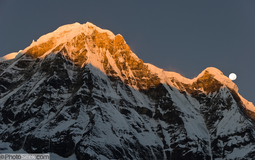 """Moon set over Annapurna South at sunrise, seen from Annapurna South Base Camp (ABC, at 13,550 feet elevation), in the Himalaya of Nepal. Annapurna South (also known as Annapurna Dakshin, or Moditse; 23,684 feet / 7219 meters). Annapurna South was first climbed in 1964 by a Japanese expedition, via the North Ridge. Annapurna is Sanskrit for """"Goddess of the Harvests."""" In Hinduism, Annapurna is a goddess of fertility and agriculture and an avatar of Durga."""