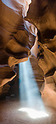 """A ray of sunlight pierces Upper Antelope Canyon, near Page, Arizona, USA. Antelope Canyon Navaho Tribal Park. Panorama stitched from three overlapping images. Published in """"Light Travel: Photography on the Go"""" book by Tom Dempsey 2009, 2010."""