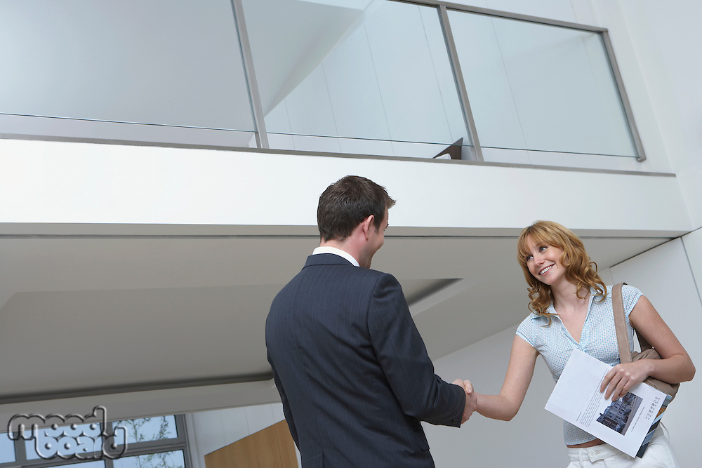 Real estate agent shaking woman's hand in new home