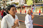 "01 FEBRUARY 2013 - PHNOM PENH, CAMBODIA: A woman mourning former Cambodian King Norodom Sihanouk walks along Sisowath Quay in Phnom Penh. Norodom Sihanouk (31 October 1922 - 15 October 2012) was the King of Cambodia from 1941 to 1955 and again from 1993 to 2004. He was the effective ruler of Cambodia from 1953 to 1970. After his second abdication in 2004, he was given the honorific of ""The King-Father of Cambodia."" Sihanouk died in Beijing, China, where he was receiving medical care, on Oct. 15, 2012. His cremation is will be on Feb. 4, 2013. Over a million people are expected to attend the service.     PHOTO BY JACK KURTZ"