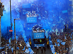 The Manchester City players and staff on the buses pass the crowds of fans gathered on the route during the trophy parade in Manchester.